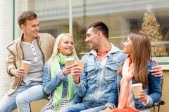 小组微笑的朋友与拿走咖啡 免版税库存图片
