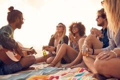 小组微笑的朋友获得乐趣在海滩 免版税库存照片