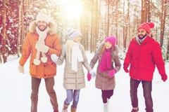 小组微笑的男人和妇女在冬天森林里 免版税库存图片