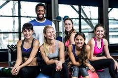 小组微笑适合的人,当坐锻炼球时 免版税库存图片