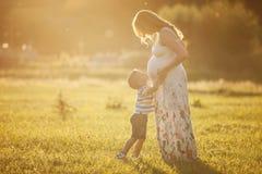 小他怀孕的母亲的男孩亲吻的腹部 免版税图库摄影