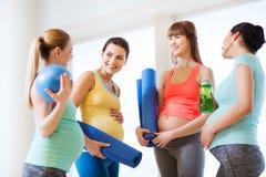 小组愉快的孕妇谈话在健身房 免版税库存图片