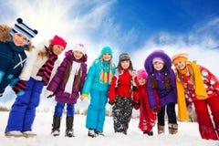 小组愉快的孩子外面在雪天 免版税图库摄影