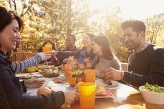 小组愉快的朋友吃并且喝在桌上在烤肉 库存照片