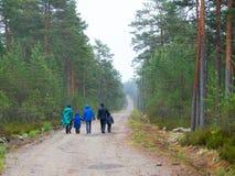 小组成人和孩子在一条路通过森林 免版税库存图片