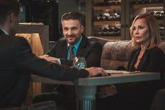 小组成功的商人谈论在工作晚餐期间在餐馆 免版税库存图片