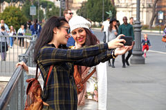 小组拍照片的海滩的快乐的年轻朋友使用selfie棍子 免版税库存图片