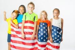 小组拿着美国国旗的小学生 免版税库存图片