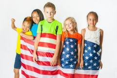 小组拿着美国国旗的小学生 库存图片