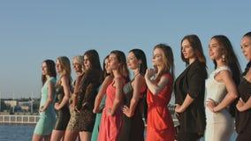 小组摆在的礼服和的脚跟的美丽的女孩,当站立在行时 股票录像