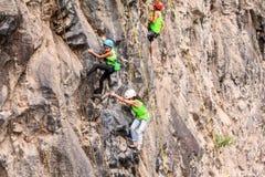 小组攀登岩石墙壁的少年登山人 免版税库存图片