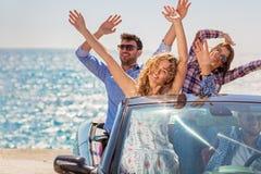 小组敞蓬车的愉快的年轻朋友用驾驶在日落的被举的手 免版税图库摄影