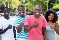 小组显示拇指的四个非裔美国人妇女和人 免版税库存图片