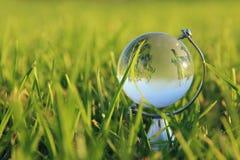 小水晶地球低角度在草的 旅行和全球性概念 库存照片