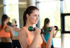 小组有哑铃的妇女在健身房 免版税图库摄影