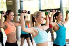 小组有哑铃的妇女在健身房 图库摄影