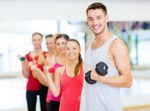 小组有哑铃的微笑的人在健身房 免版税库存照片