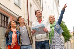 小组有地图探索的城市的微笑的朋友 免版税库存图片