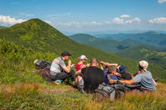 小组有大背包的游人在山放松 免版税库存图片