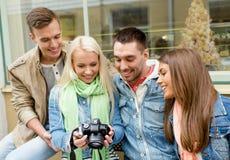 小组有数字式photocamera的微笑的朋友 免版税库存图片