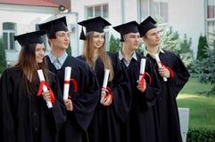 小组有文凭的毕业生在他们的手上 免版税库存照片