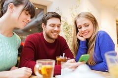 小组有智能手机会议的朋友在咖啡馆 免版税图库摄影