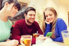 小组有智能手机会议的朋友在咖啡馆 免版税库存照片
