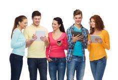 小组有智能手机和片剂个人计算机的少年 免版税库存照片