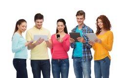 小组有智能手机和片剂个人计算机的少年 库存照片