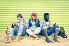小组有智能手机的年轻多种族朋友在海滩 免版税库存图片