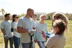 小组有树幼木的志愿者在公园 免版税图库摄影