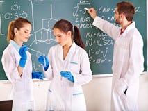小组有烧瓶的化学学生。 免版税库存图片