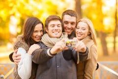 小组有照片照相机的朋友在秋天公园 免版税库存照片