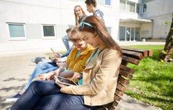 小组有片剂个人计算机的学生在校园 免版税库存照片