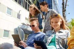 小组有片剂个人计算机的学生在校园 库存照片