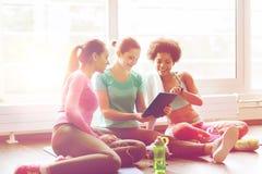 小组有片剂个人计算机的愉快的妇女在健身房 库存照片