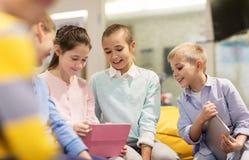 小组有片剂个人计算机的愉快的孩子在学校 图库摄影