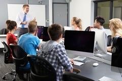 小组有男性家庭教师的学生计算机类的 免版税库存图片