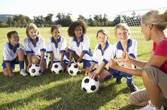 小组有的足球队员的孩子与女性教练的训练 免版税库存图片