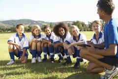 小组有的足球队员的孩子与教练的训练 免版税库存图片
