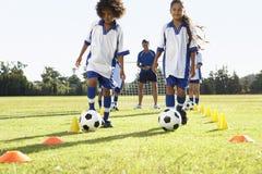 小组有的足球队员的孩子与教练的训练 免版税图库摄影