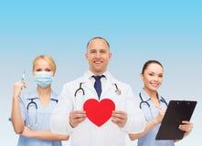 小组有红色心脏形状的微笑的医生 免版税库存图片