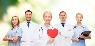 小组有红色心脏形状的微笑的医生 库存照片