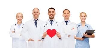 小组有红色心脏形状的微笑的医生 库存图片