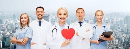 小组有红色心脏形状的微笑的医生 免版税库存照片