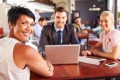 小组有膝上型计算机会议的商人在咖啡店 免版税库存图片