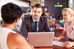 小组有膝上型计算机会议的商人在咖啡店 免版税库存照片