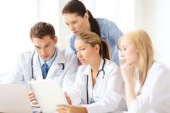 小组有膝上型计算机和片剂个人计算机的医生 库存照片