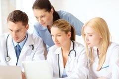 小组有膝上型计算机和片剂个人计算机的医生 免版税库存图片