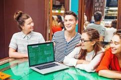 小组有膝上型计算机的愉快的人在咖啡馆 库存照片
